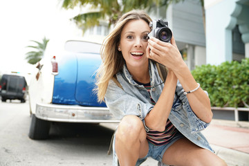 Attractive photographer taking photos with vintage camera in city