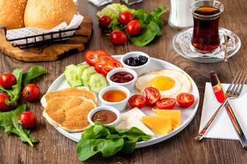 Huge healthy breakfast spread on a table with coffee, tea, tomato, egg, pancake, jam and cheese,