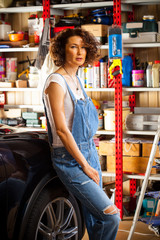 curly-haired woman in blue overalls mechanic near a car