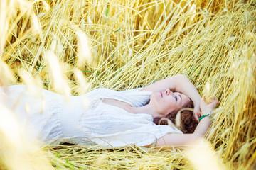 woman in white dress lies in a field among ears of corn