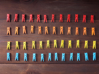 Red, orange, blue, yellow pegs in rows on brown wooden background
