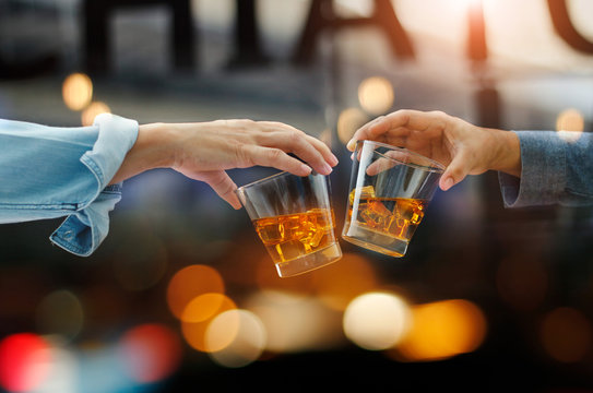Close-up of two men clink glasses of whiskey drink alcoholic beverage together while at bar counter in the pub after work on colorful background