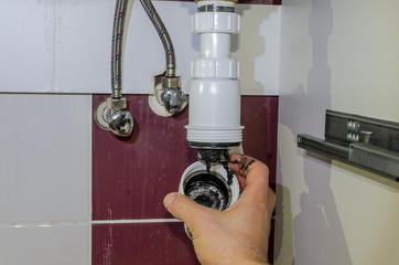 Plumber cleans sewer drain in siphon under sink