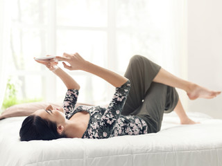 Young woman relaxing on the bed and connecting