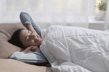 Happy relaxed woman waking up early in the morning