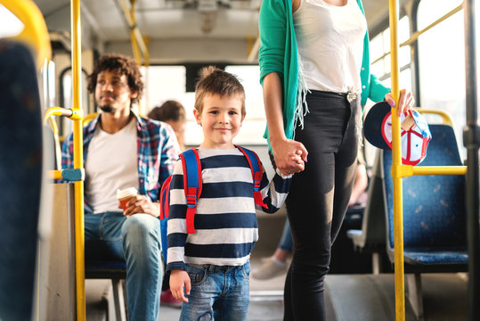 Mom holding son's hand and standing in the the public transportation. Kid looking at camera.
