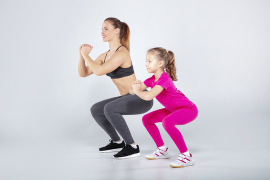 Female trainer and 10 years old girl are doing gym exercises