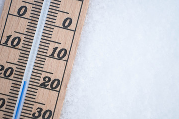wooden thermometer in snow with freezing temperature copy space