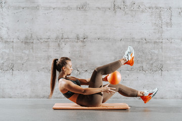 Side view of muscular powerful woman with ponytail and in sportswear doing abs with ball on the mat in front of gray wall.