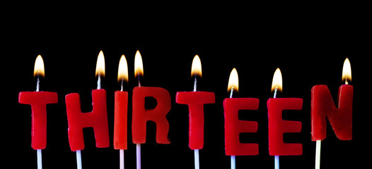 Thirteen spellt out in red birthday candles against a black background