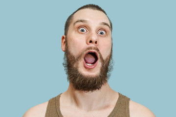 Very surprised scared funny face of a bearded guy with open mouth and big eyes on an isolated background