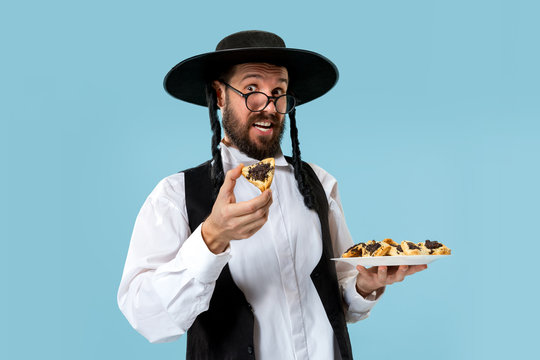The young orthodox Jewish man with black hat with Hamantaschen cookies for Jewish festival of Purim at studio. The purim, jewish, festival, holiday, celebration, judaism, pastry, tradition, cookie