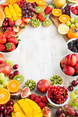 Wall Mural - Healthy raw background, cut fruits, strawberries raspberries oranges plums apples kiwis grapes blueberries mango persimmon, on white table, copy space, selective focus