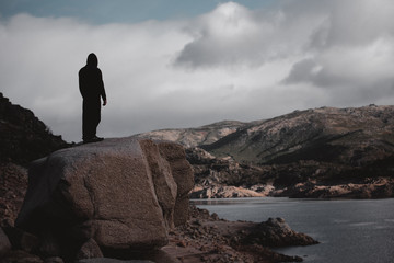 Back view of unrecognizable man standing on big stone at the river in hillside in Portugal