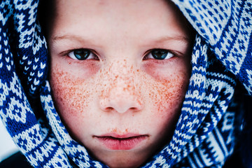 Portrait of boy with freckles wrapped in scarf