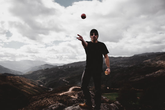 Handsome man throwing up apple while standing on the top of the hill in Portugal