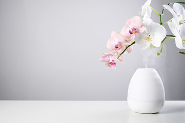 Ultrasonic Oil diffuser and orchid flowers on white table of gray background