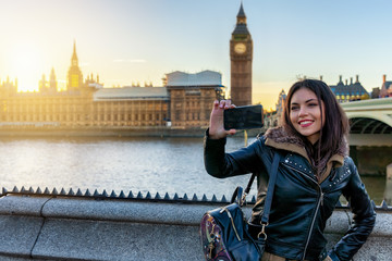 Attraktive Touristin in London macht ein Selfie Foto von sich vor dem Big Ben Turm bei Sonnenuntergang
