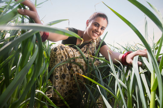 Smiling woman farmer standing in her agriculture field touching the tall grass.