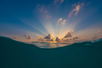 Sunset in clouds over sea water, waterline slpits two environmental space, tropical water background