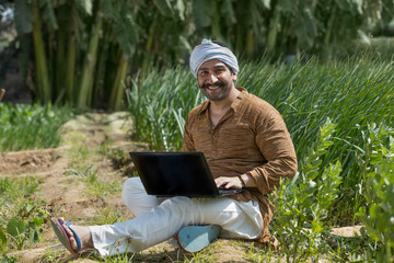 Happy farmer or village man operating a laptop computer in his agriculture field.