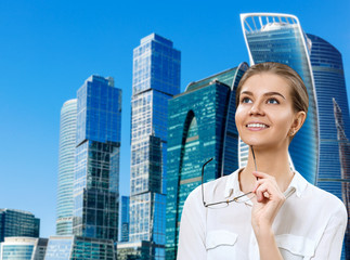Young business woman holds glasses and looking up with inspiration