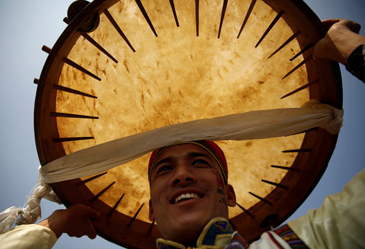 A man dressed in traditional attire holds a drum above his head as he sings and dances during the Sonam Lhosar in Kathmandu