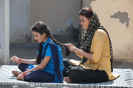 Village woman braiding the hair of her school going daughter sitting on a cot in their house.