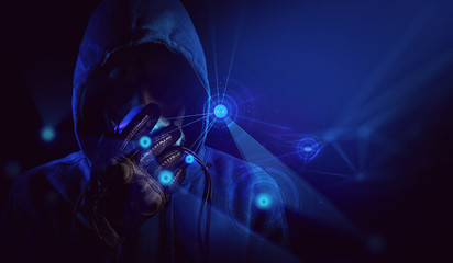 bad guy hacker with blue hood outfit and mask with glove on dark background in security virus network hologram concept