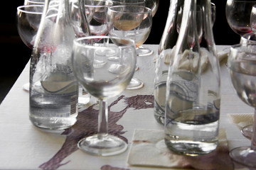 Wine glasses and bottles on the table after the exhibition opening and presentation.
