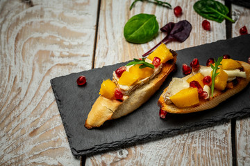 Two fresh bruschettes with with mango, Camembert cheese and pomegranate on a shale board, white wooden background. Top view