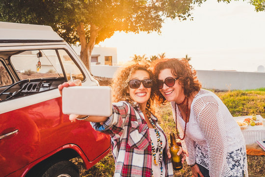 Nice attractive couple of middle age woman travel together with old red van vintage and take selfie with modern phone during outdoor picnic leisure activity - sunny day of summer vacation