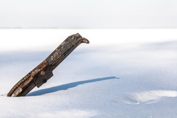 Rusty pipe sticks out from under a thick layer of white snow in the lake