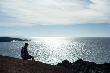A man looks at the sea, sitting on a stone.