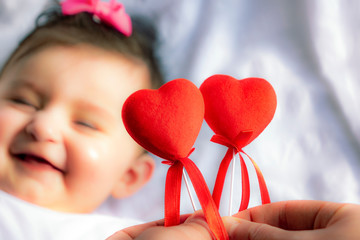 Valentine's day picture of smiling baby on a hearts that says be mine on white fabric surface