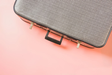 Vintage suitcase for travel on pastel pink. Concept vacations. Top view with copy space.