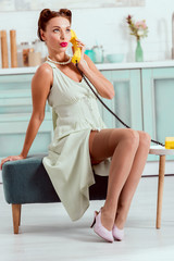 Pretty pin up girl sitting on ottoman and talking on vintage yellow phone