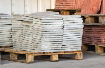 Paving slabs factory. Tiles piled in pallets.