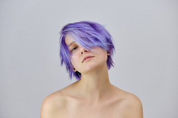 A beautiful girl with purple hair sits in the middle of the photo with a gray background and grimaces. She's naked and visible shoulders.