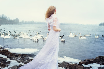 girl in a vintage dress on a river in winter