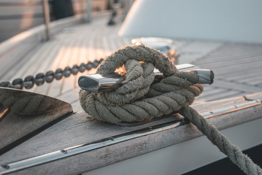 Close-up of detailed knotted rope on a luxury wooden sailboat yacht laying in a harbour