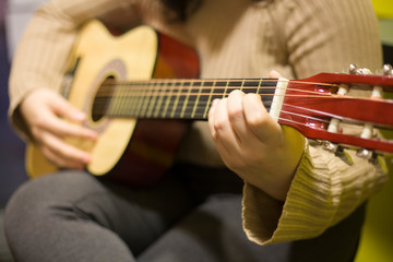 The girl plays the guitar. A guitar lesson. A music shop