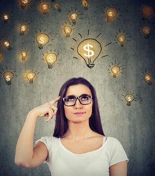 woman looking up at dollar idea light bulbs above head deciding how to earn morney