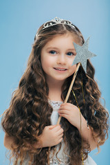 Image of attractive small child with curly dark hair, holds magic wand, looks happily into distance, beileves in miracle, isolated over blue background. Cute pretty little girl stands indoor