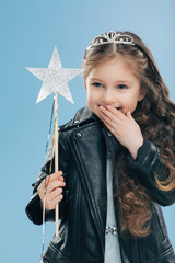 Glad pleasant looking small kid covers mouth with palm, giggles positively, wears crown and black leather jacket, holds magic wand, isolated over blue background. Children and happiness concept