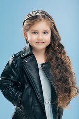Vertical shot of attractive small female child has long curly hair, wears crown and leather jacket smiles positively isolated over blue wall. Happy little girl dressed in stylish clothes models indoor
