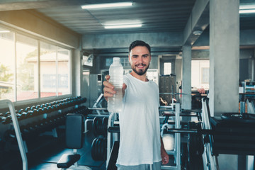 Portrait of sporty male holding bottle of water to giving someone in front of camera on exercise equipment background., Smiling sports man working out in gym.,Sport club and healthy concept.