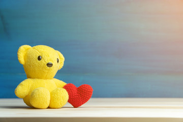 hand make yarn red heart beside yellow teddy bear on wooden table and blue background. Concept of valentines day.