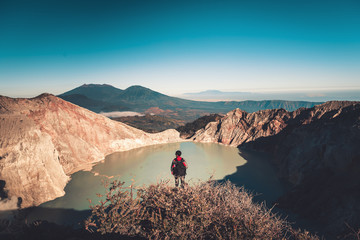 Traveler photography is standing beside of the crater at Kawah Ijen volcano, National Park of Indonesia.,Outdoor adventure traveling destination., Hobbies and leisure activities concept.