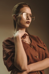 attractive stylish woman posing in glasses isolated on brown
